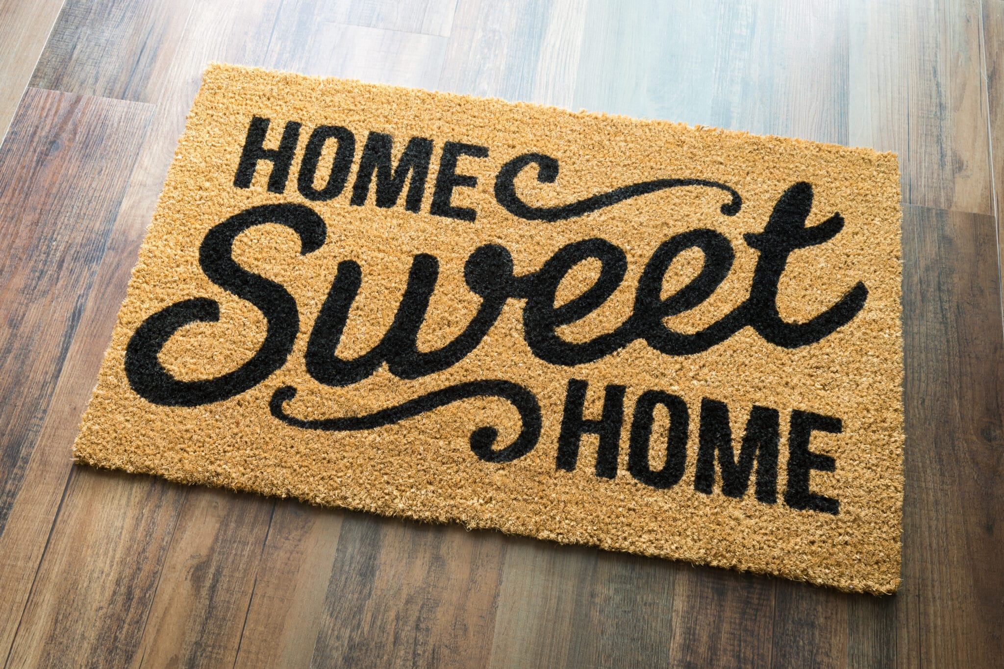 Home Sweet Home Welcome Mat On Wood Floor.